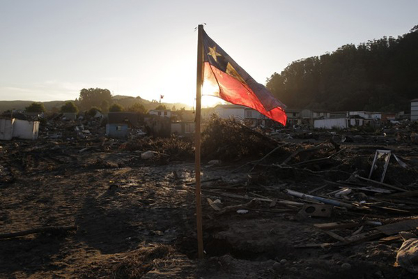 A Chilean flag flies on a beach where a massive earthquake and ensuing tsunami caused widespread destruction in Constitution